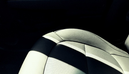 industry: Light shadows across a black leather car seat .