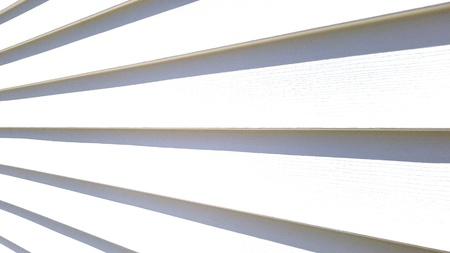 White vinyl siding on a house in the light.
