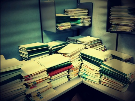 dark: A dark office cubicle concept of stacks of file folders piled together on a desk.