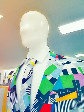 Mens clothing store mannequin dressed up in a flashy colored suit.
