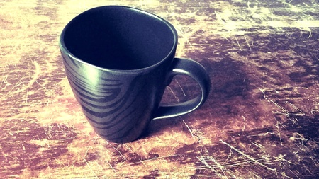 Black coffee cup on a scratched wooden table. Stock Photo
