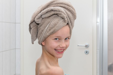 A girl is standing in the bathroom, wrapping the towel in a turban, portrait