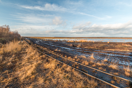 Landscape shot of a peat mining area with rails of a peat railway