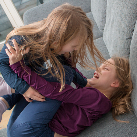 A 7- and a 9-year-old girl scream at each other and beat each other