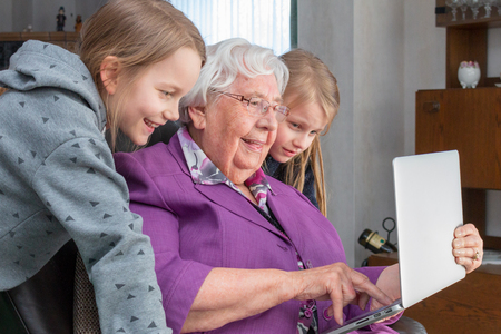 A 95 year old woman is holding a laptop  and showing her grandchildren something funny. She is sitting on a armchair in her living room and they are  looking at the screen Imagens