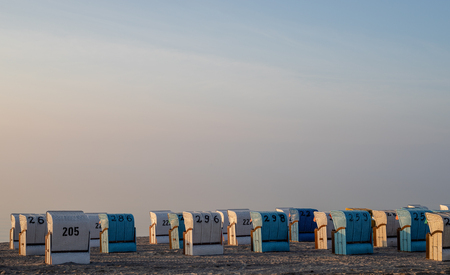 landscape shot of white and blue colored roofed beach chair at baltic sea beach in the morning with copy space