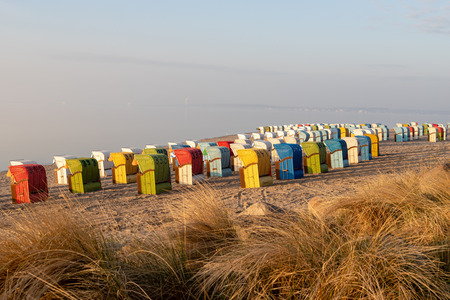Landscape shot of colourful roofed beach chair at baltic sea beach in the morning with grass in the foreground