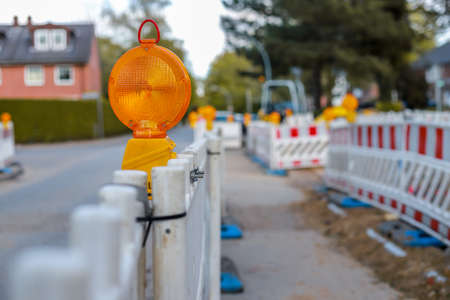 住宅地の通りで警告灯が付いた赤と白のバリケード、被写界深度