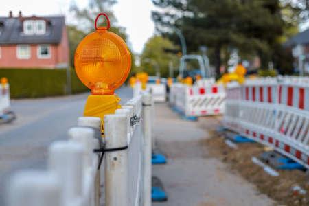 Barricadas rojas y blancas con luces de advertencia en una calle de la zona residencial, profundidad de campo