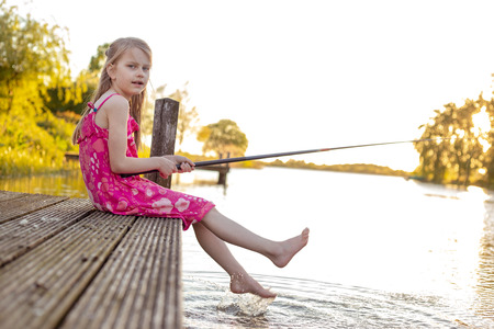 A 7 year old girl is sitting with her fishing rod on a jetty by a lake, waiting for a fish to bite. She looks into the camera and splashes with her feet in the water