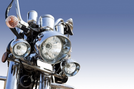 front angle: Front part of a vintage motorbike against blue. Low angle view.