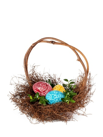 Basket with Easter eggs and boxwood twigs against white  photo