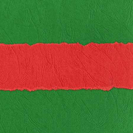 Red horizontal strip of torn paper on green  photo