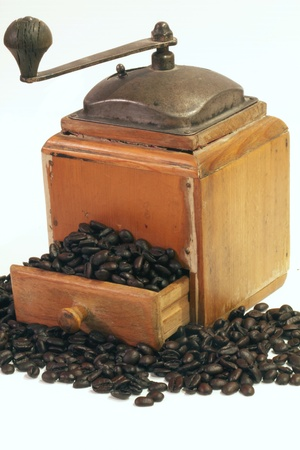 Antique coffee grinder on white background with beans spilling out of the tray Reklamní fotografie