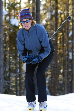 Female cross country skier in the trees skiing downhill on snow