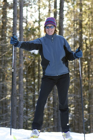 Baby boomer female cross country skier with back lighting in the trees photo