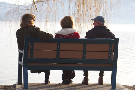 sinlight: Famiily of three sitting on a park bench, photographed from behind in sinlight Stock Photo
