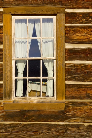 damaged roof: Portrait of old log cabin window with square log detail and chinking