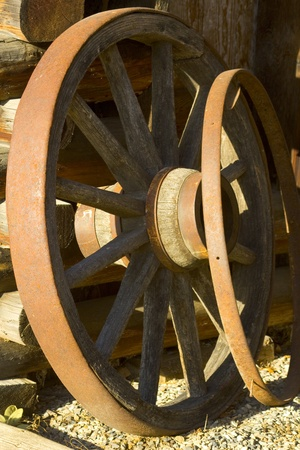 Antique wagon wheels leaning against an old square log barn photo