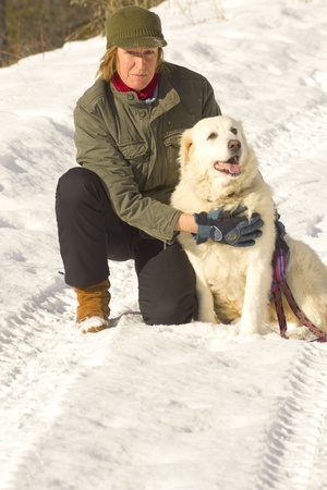woman kneeling: Woman kneeling down with dog at her side in winter.