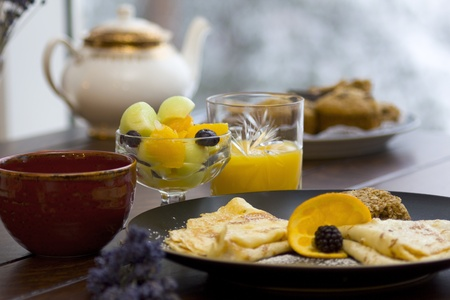 served: Fresh fruit breakfast served with tea and crepes Stock Photo