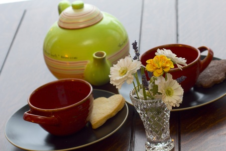 Pot of tea on a table with fresh baked cookies and flowers photo