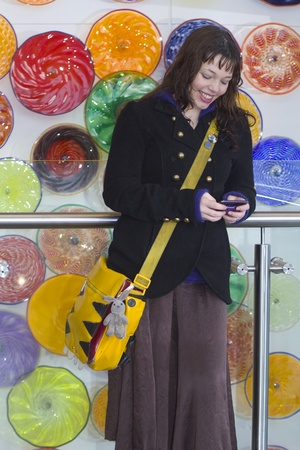 Young smiling woman texting on a phone with colourful art in the background photo