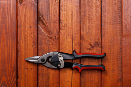 snips: tin snips with black and red plastic insulated handles on a wood background