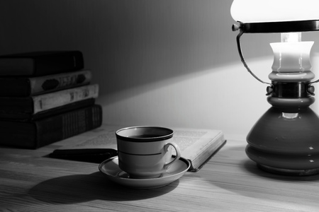 tea lamp: Cup of tea and stack of old books on the table with lamp. Black and white.