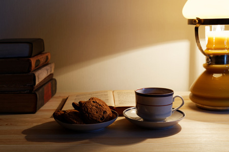tea lamp: Cup of tea and stack of old books on the table with warm lighting lamp