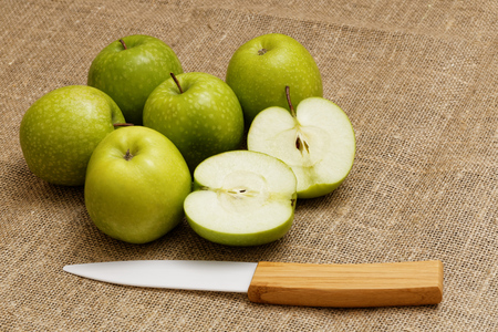 bagging: Six small green apple and ceramic knife  on the bagging