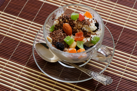 icecream with raisins, chocolate and dry fruits in glass cup photo