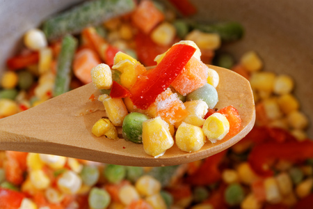 Closeup wooden spoon with frozen mixed vegetables