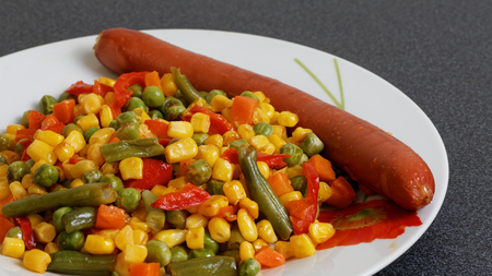 weenie: Sausage and fried colorful mixed vegetables, closeup