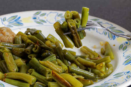 Closeup fork with fried green french bean (haricot vert)