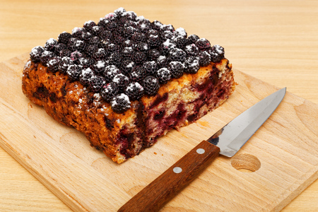 black raspberries: Closeup part of cake with black raspberries and knife on the kitchen cutting board. Stock Photo