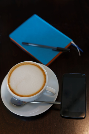 shallow  focus: Cup of cappuccino, smartphone and notebook with pen on the table. Shallow focus on coffee.
