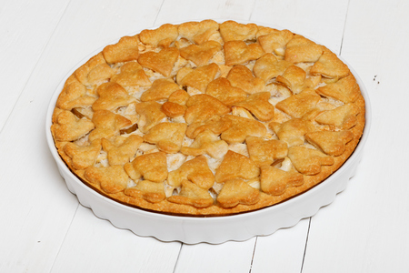 angle view: Homemade pie with apples and pears decorated with hearts on white wooden table. Angle view. Stock Photo