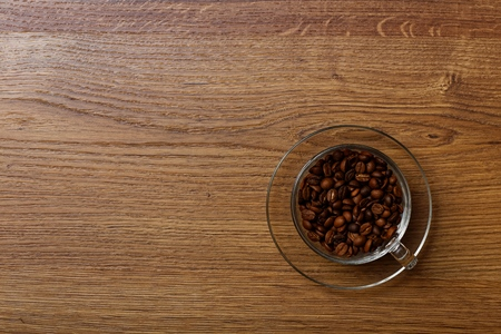 coffee table: Transparent cup with coffee beans on a wooden table Stock Photo