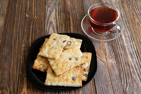 angle view: Cookies with raisins and cup of tea on the dark brown wooden table. Angle view. Stock Photo