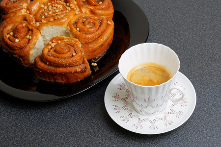 shallow  focus: Cup of coffee and cinnamon bun with caramel syrup. Shallow focus.