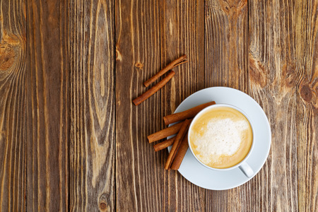 White Cup of hot Cappuccino and Cinnamon on brown wooden table. Top view.