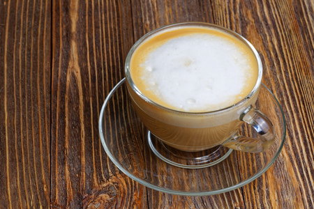 cappuccino cup: Glass transparent cup with cappuccino on wooden table
