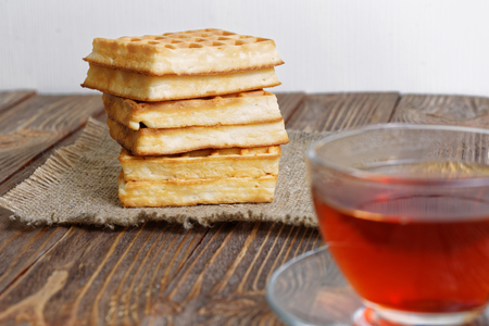 shallow  focus: Stack of waffles on a napkin of burlap and a cup of tea on a wooden table. Shallow focus.