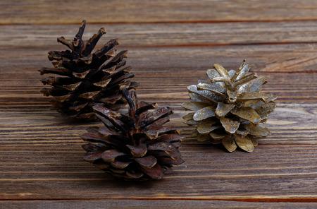 pine three: Closeup three pine cones on brown wooden background Stock Photo