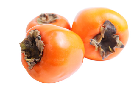 shallow  focus: Three ripe persimmons isolated on white. Shallow focus.