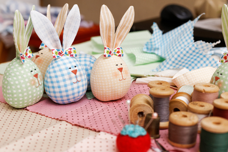 shallow  focus: Handmade bunnies, spools of thread and a needle on a piece of cloth. Shallow focus. Stock Photo