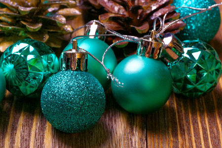 shallow  focus: Christmas balls and pinecone on wooden background. Shallow focus.