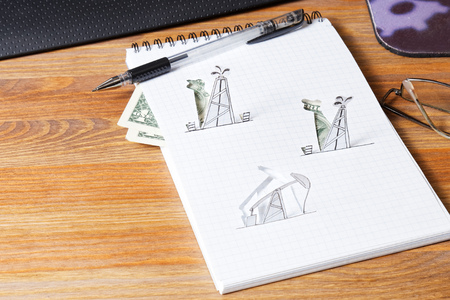 beam pump: Petroleum pumpjack and oil rigs. Concept from paper on the table.