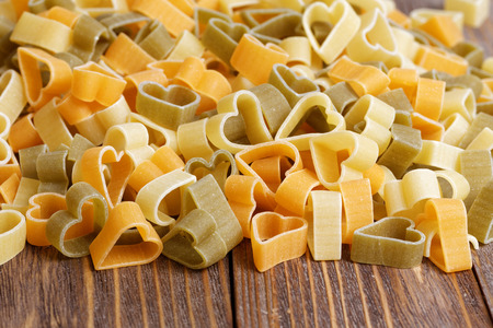 durum: Durum wheat heart-shaped pasta with vegetables on wooden background for Valentine Day. Stock Photo